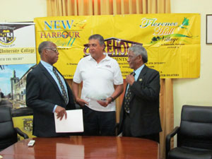 Mr Phillip Gore (centre) speaks with Carl James Chairman of the Board of Directors MICO (left) and Mr. Neville Ying, Chairman of the MICO Foundation (right).